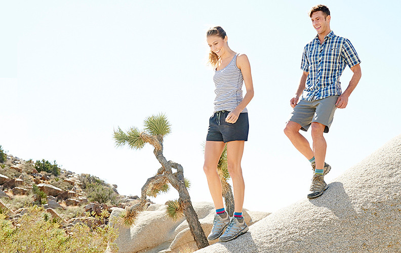Two people are shown hiking in Joshua Tree National Park