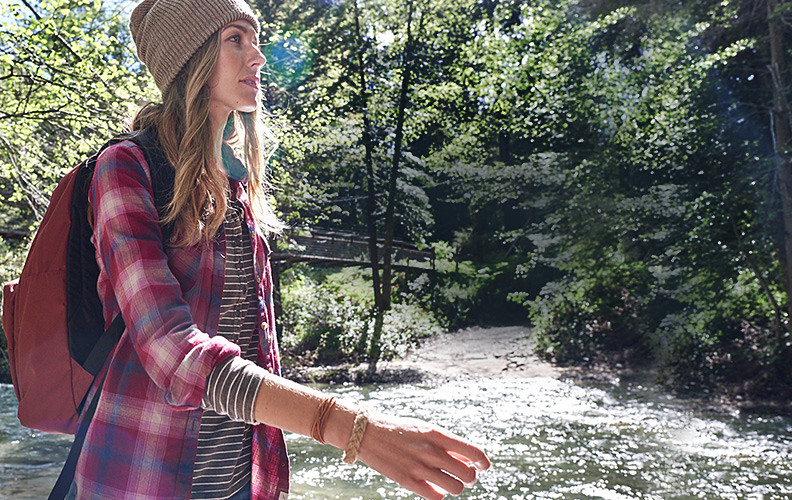 Woman wearing a flannel shirt hiking beside a river