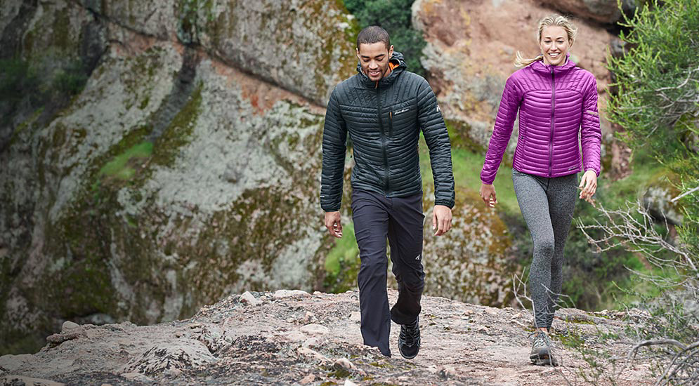 Two people wearing MicroTherm Jackets on a fall hike