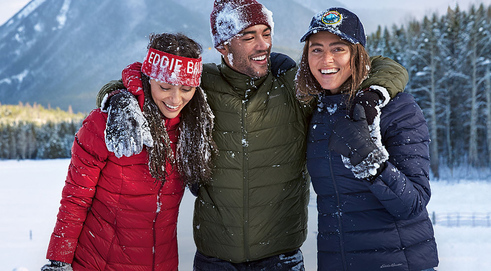 Three people in down jackets enjoy a snowy landscape