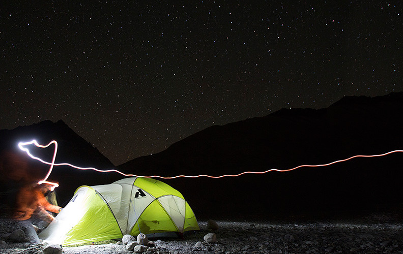 Illuminated tent in a dark winter landscape