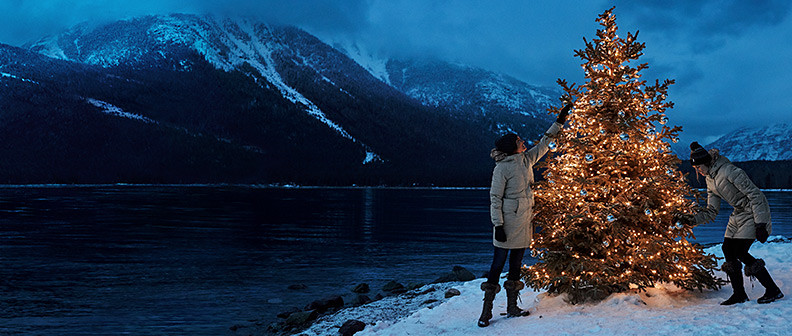 Two people decorating a christmas tree in a winter landscape
