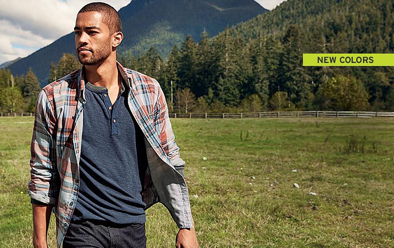 A man in a plaid shirt walks in an open field
