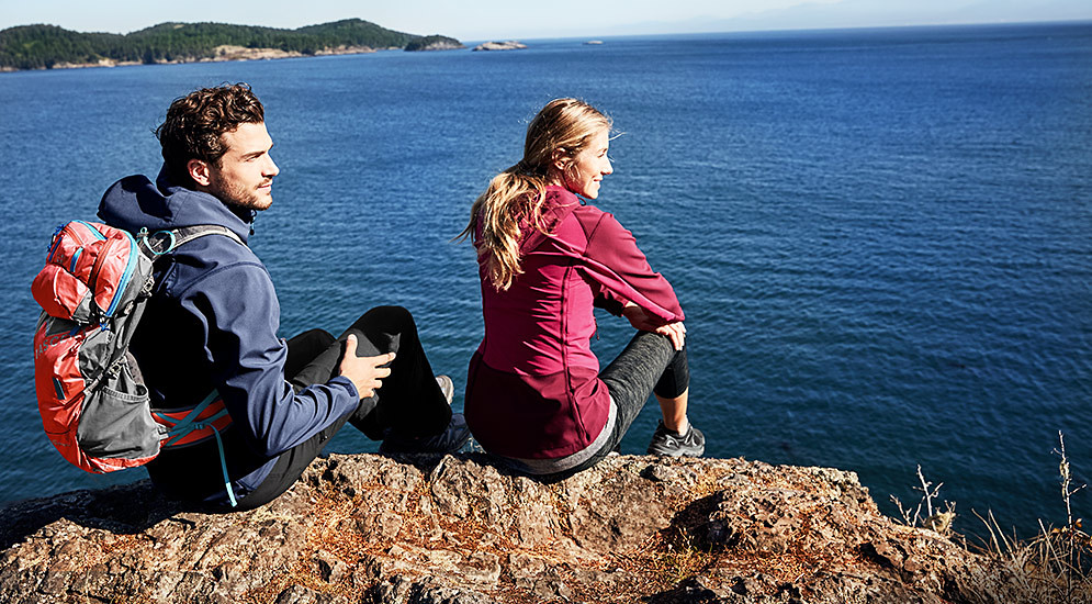Two hikers sit on a rock overlooking the water