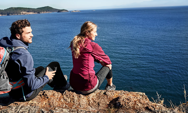 A man and a woman in hiking clothes sit on a rock overlooking the water
