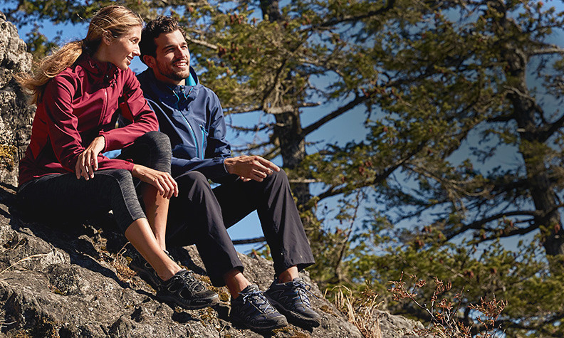 A man and a women in hiking clothes sit on a rock in the sun