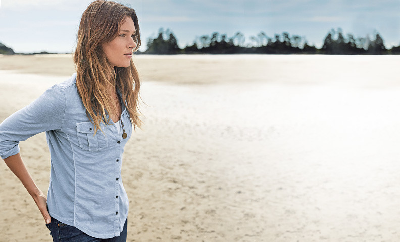 A women in a blue shirt stands on a sandy beach