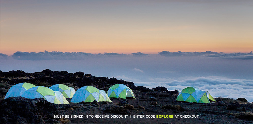 A group of tents at a high altitude basecamp are silhouetted against a sunset