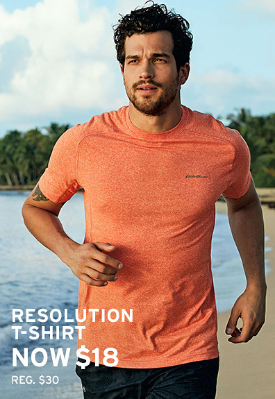 A man wearing a Resolution T-Shirt runs on the beach