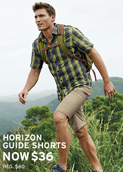 A man in Guide Pro Shorts hikes up a hill