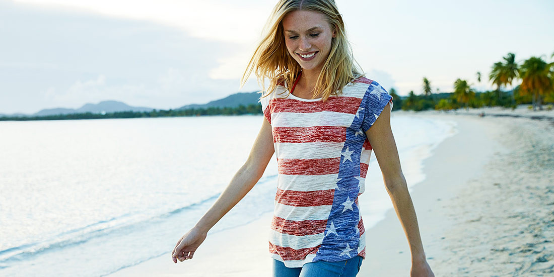 Image of a woman on the beach wearing the flag T-shirt