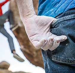Image of a man rock climbing in jeans