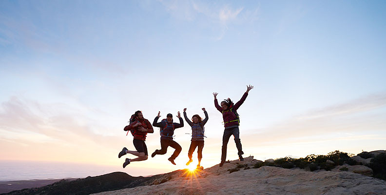 Four hikers jumping in the air