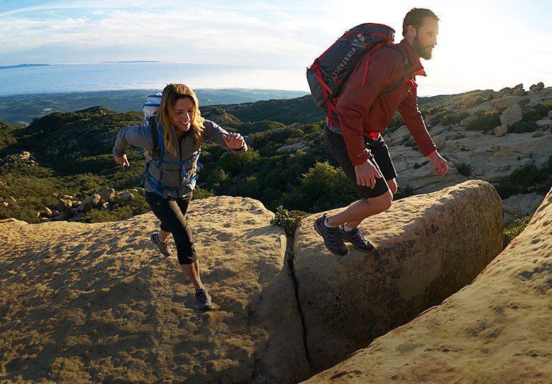 Image of two people with backpacks hiking up a hill