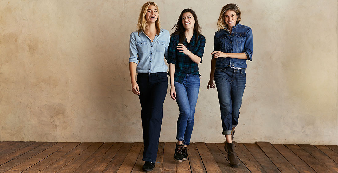 Three women wearing different styles of jeans