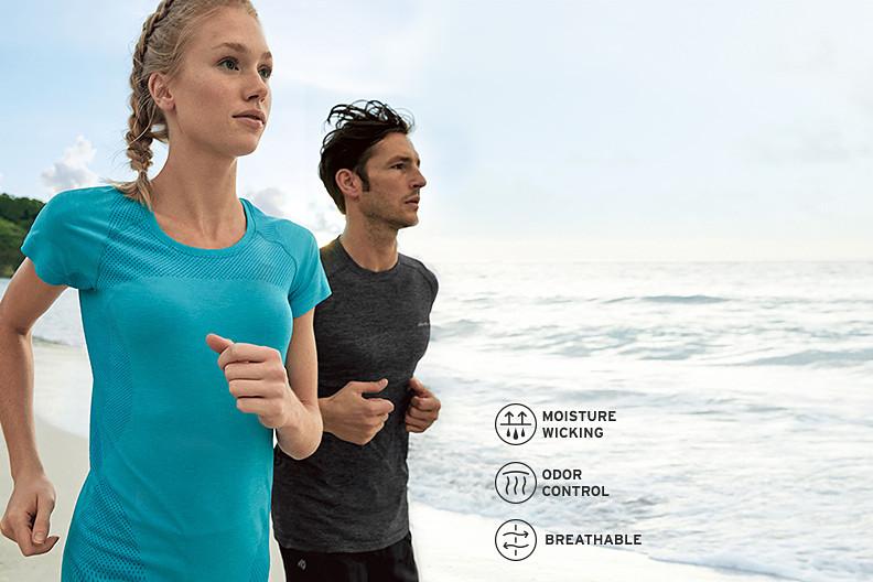 A man and a woman wearing Resolution Flux T-shirts run on the beach