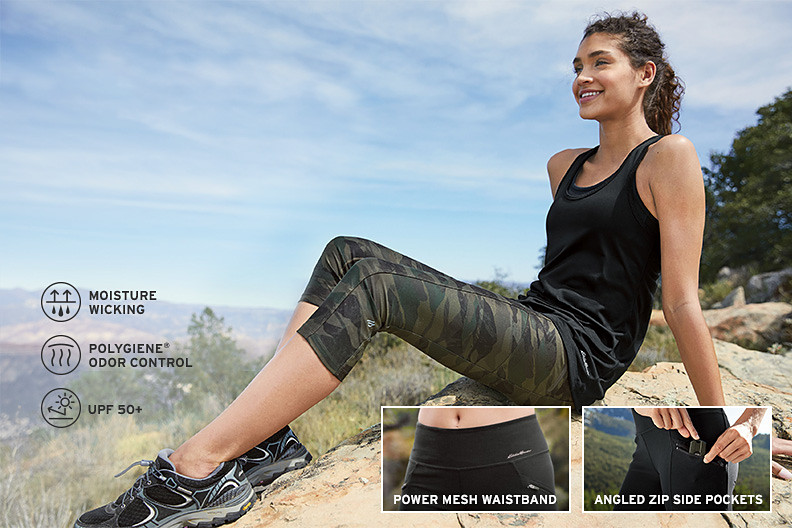 A woman wearing trail tights and a tank top takes a break from hiking