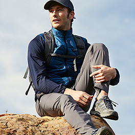 A man with a backpack takes a break from a hike