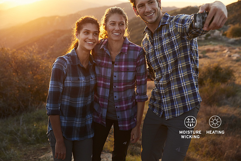 Three people in flannel shirts take a selfie while hiking
