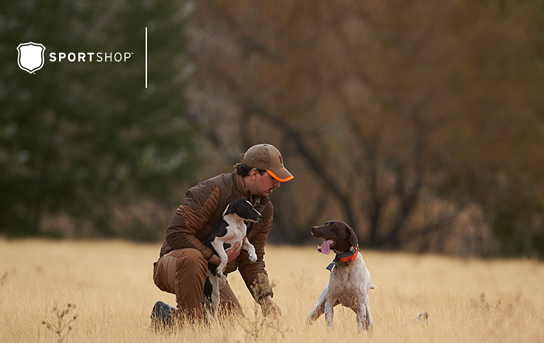 A man wearing a Sport Shop Field Jacket kneels in a field with his two hunting dogs