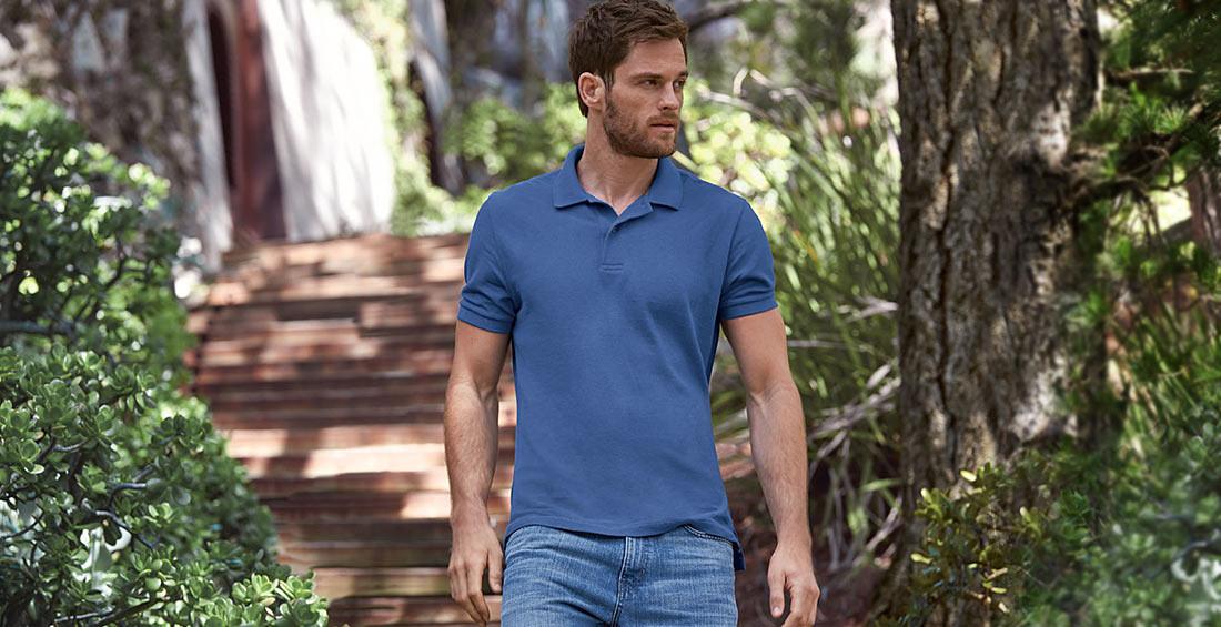 A man in a Field Polo walks down a wooded path