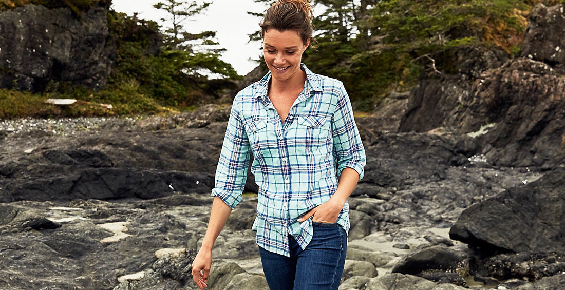 A woman in a packable shirt walks on a rocky beach