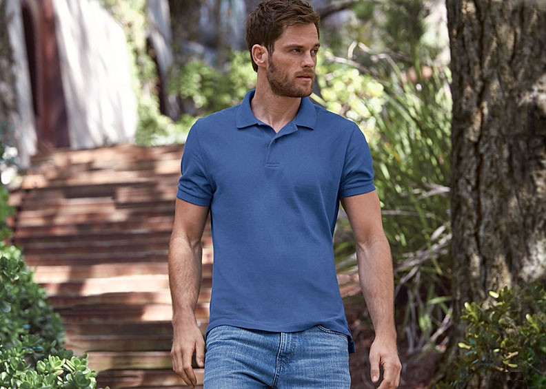 A man wearing a polo walks down a wooded path