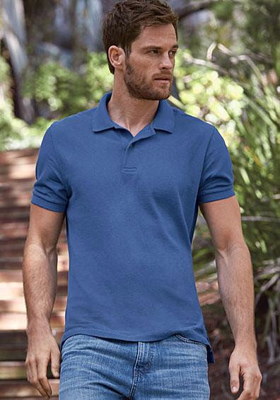 A man wearing a field polo walks down a wooded path