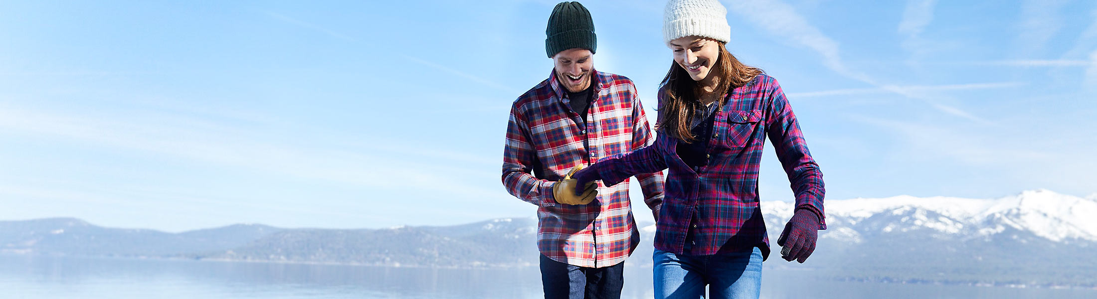 A man and a woman wearing flannel shirts hike near a lake