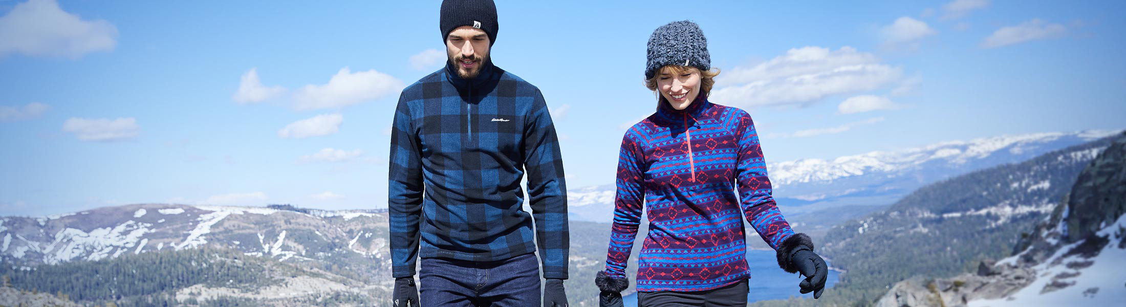A man and a woman in quest fleece pullovers hike up hill with mountains behind them