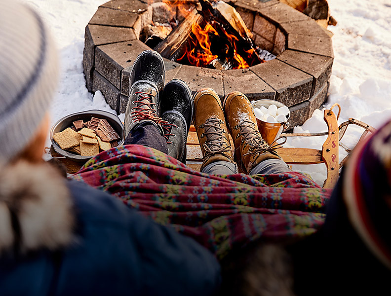A man and a woman wearing boots prop their feet up by a campfire