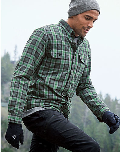 A man wearing Expedition Flannel hikes in the woods