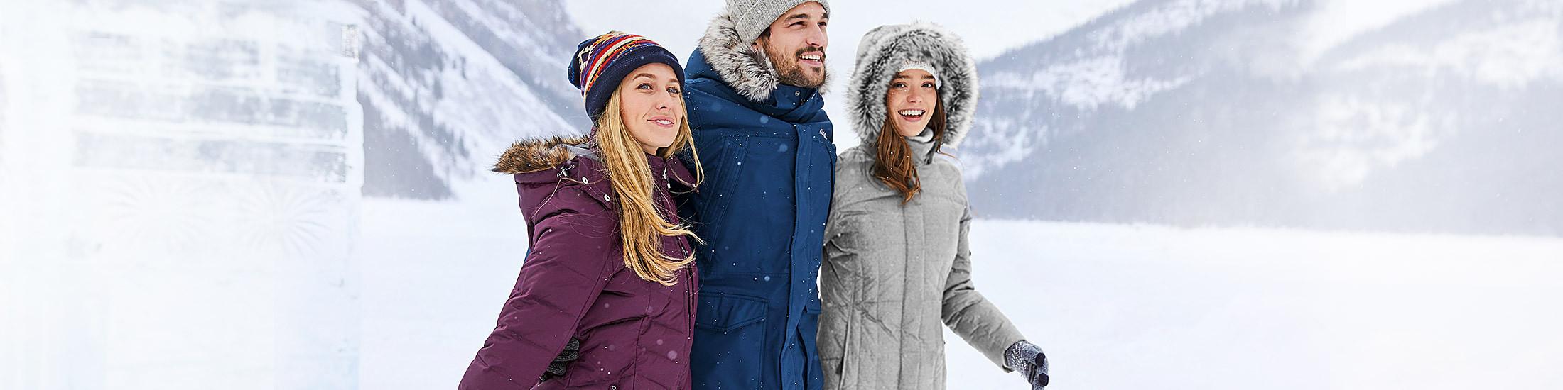 Three people wearing down parkas walk in a snowy landscape