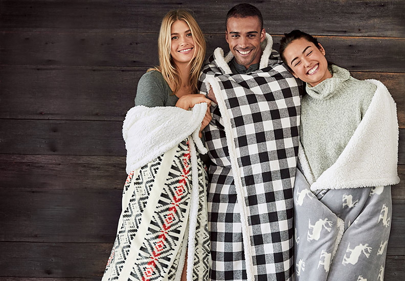 Three people wrapped in fleece blankets stand next to each other