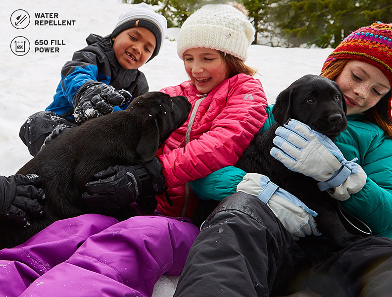 Three kids wearing down jackets play with puppies in the snow