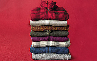 A stack of fleece jackets, showing different colors and patterns