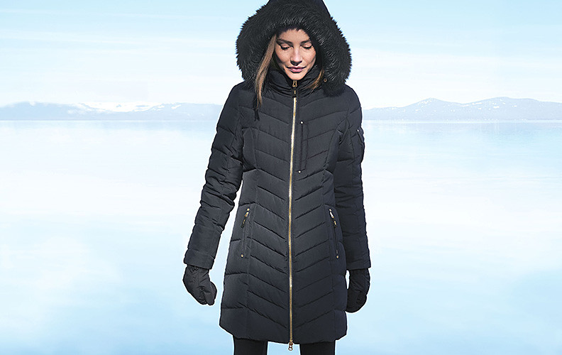 A woman in a Limited Edition Sun Valley Down Parka stands by a lake