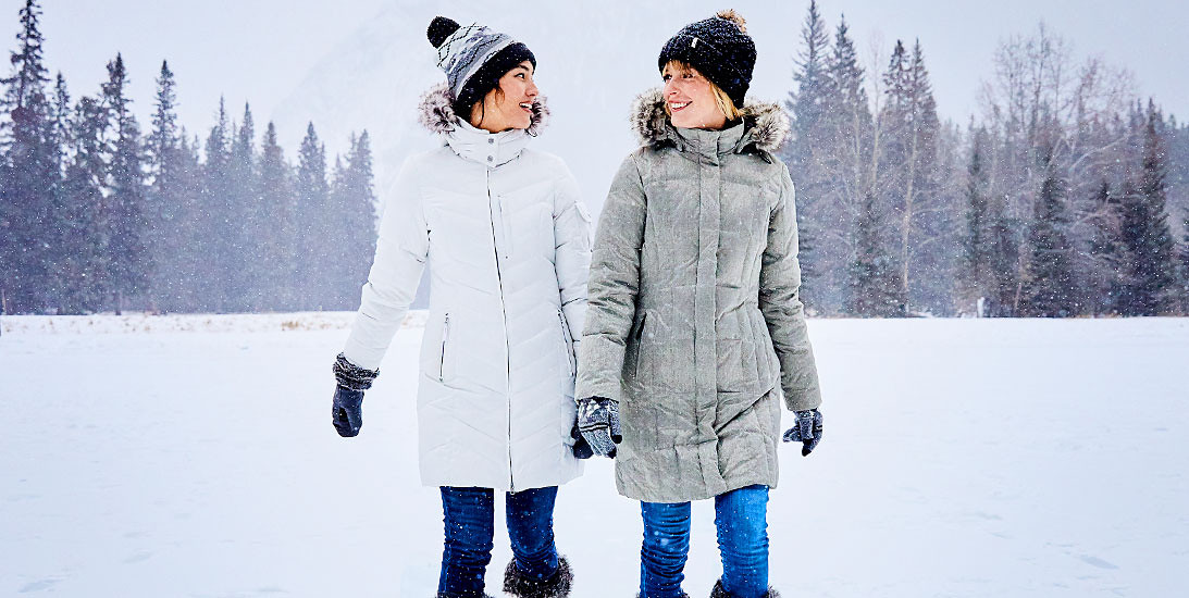 Two woman wearing down parkas stand in a snowy landscape