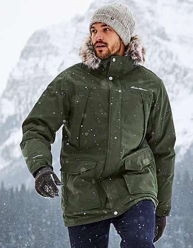 A man wearing a Superior Down Parka hikes in the snow