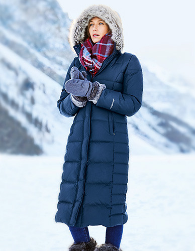 A woman wearing a lodge down duffle coat stands in a snowy landscape