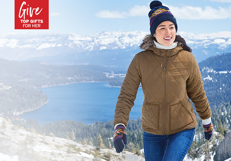 A woman in a Snowfurry Jacket hikes up a hill with mountains in the background