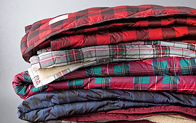 A stack of down throws showing different colors and patterns
