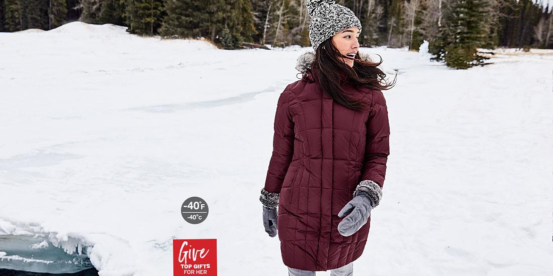 A woman wearing a Lodge Down Parka walks in a snowy landscape