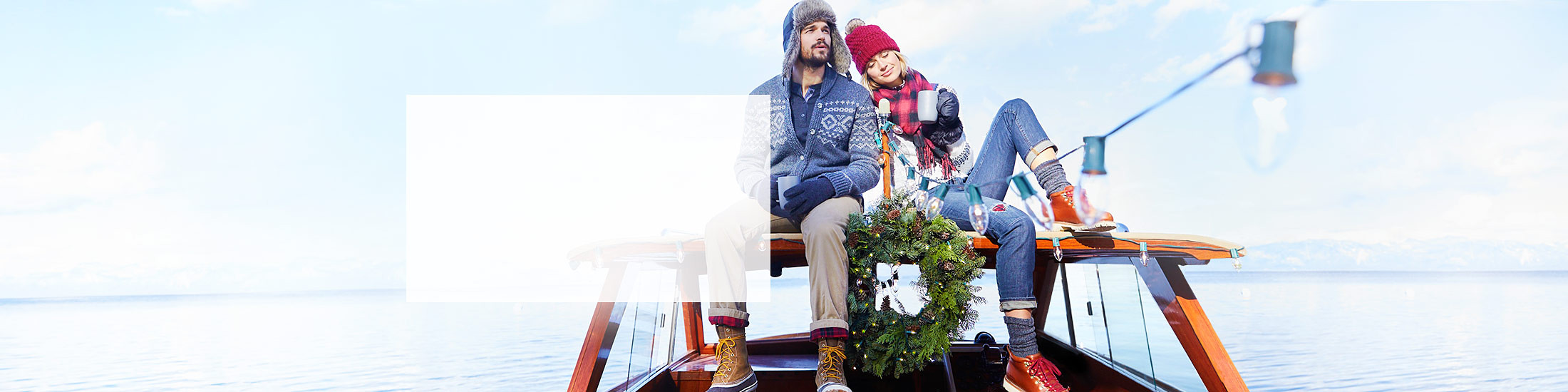 A man and a woman sit on a boat decorated for the holidays