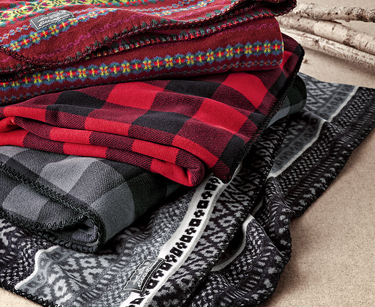 A stack of Quest Fleece Throws in different colors and patterns