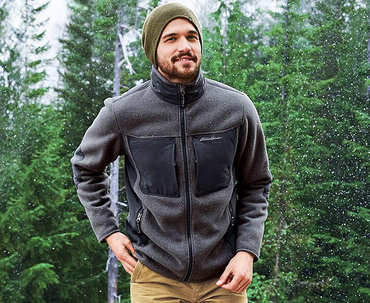 A man wearing a Crux Fleece Jacket walks in the snow