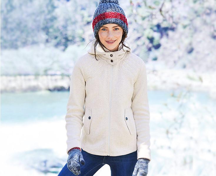 A woman wearing a Radiator Fleece jacket stands by a frozen lake