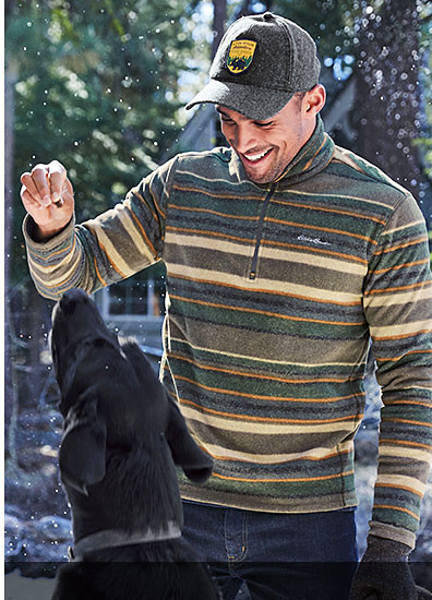 A man wearing a Quest Fleece 1/4-Zip Pullover playing with a black lab