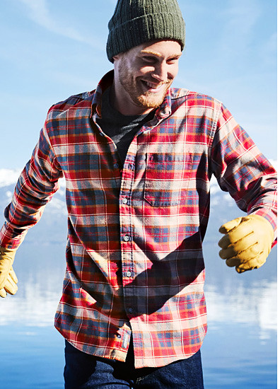 A man in a flannel shirt stands by a lake