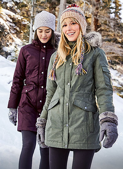 Two women wearing Superior Down Parkas walk in the snow